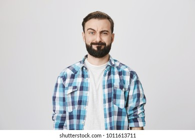 Portrait of funny disappointed bearded man, lifting his eyebrow and fake smiling while looking at camera, over gray background. Stomach rumbles during business meeting. Guy feels embarrassed