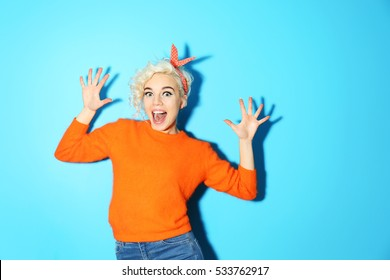 Portrait of funny emotional girl on blue background