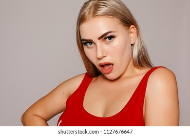 Portrait of funny emotional girl. Pretty smiling joyfully female with fair hair looking with satisfaction at camera, being happy. Studio shot of good-looking beautiful woman against blank studio wall.