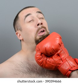 Portrait of funny fat boxer getting punch in face against gray background