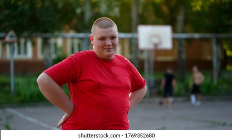 Portrait of funny fat teenager in red shirt with buzz cut. Boy standing with his arms on hips