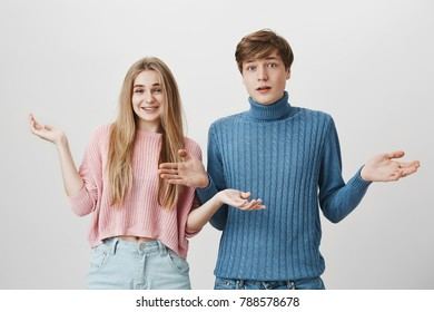 Portrait of funny friendly-looking positive European male and female in love dressed causally having confused and clueless expressions, shrugging shoulders, asking: So what?Things happen.
