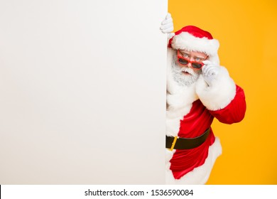 Portrait of funny funky santa claus in red headwear look behind white billboard wonder incredible 2020 christmas magic advents wear stylish black belt isolated over yellow color background