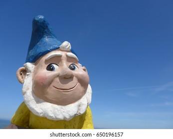 Portrait of a funny garden dwarf against blue sky