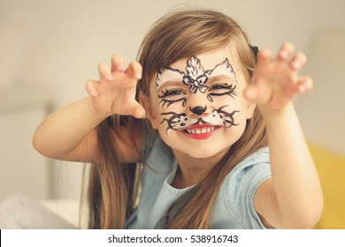Portrait of funny girl with face painting on blurred background