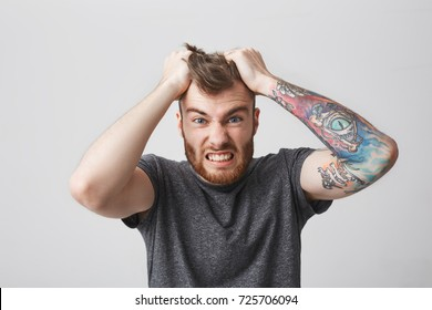 Portrait of funny good-looking bearded caucasian man with tattoo on left arm and stylish hairstyle holding hair with hands with and expression. Guy being angry his favourite football team lost.