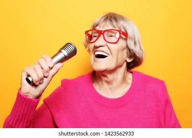 Portrait of funny grandmother holds up the microphone stand and sings isolated on vivid yellow background