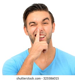 Portrait of a funny guy with finger in his nose against white background
