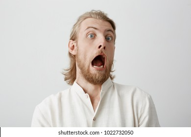 Portrait of funny handsome bearded man with fair hair, expressing shock or being terrified of something, standing with opened mouth and popped eyes over gray background. Guy is pale as if he saw ghost