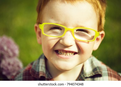 Portrait of funny happy smiling cute little boy with red hair in checkered shirt and yellow glasses sunny day outdoor on blurred natural background, horizontal picture