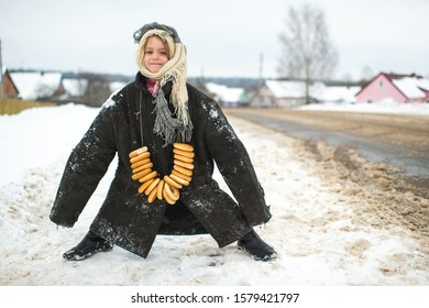Portrait of funny and humorous girl in oversized worn jacket wearing bagels on her neck in winter day.. Slavonic traditions. Happy child in loose fit clothes posing on the road.