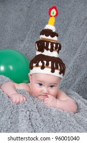 Portrait of a funny kid with the cap in the form of a cake on his head.