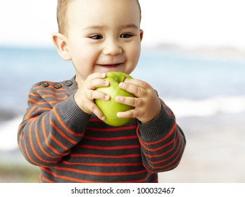 portrait of a funny kid holding a green apple and smiling near the shore