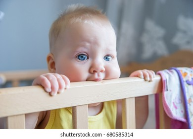 Portrait of funny kid  standing up in her crib in the room.