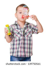 Portrait of funny little boy blowing soap bubbles isolated on white background