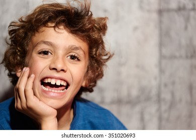 Portrait of funny little boy making faces against of grey background