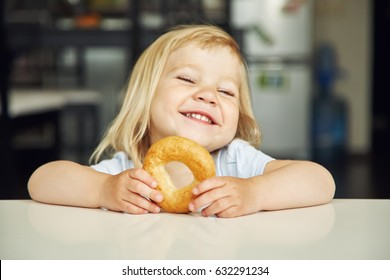 portrait of a funny little girl with bagel. child playing at home