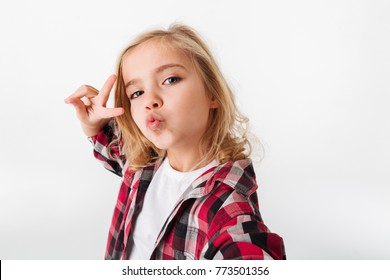 Portrait of a funny little girl grimacing while taking a selfie isolated over white background