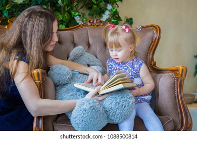 Portrait of funny little girl and her mother at home. Family, childhood and leisure concept