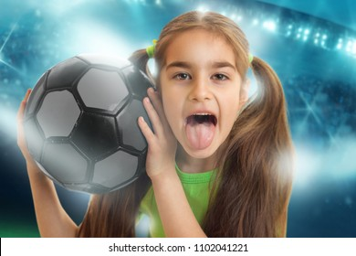 Portrait of a funny little girl with a soccer ball shows tonque at football stadium