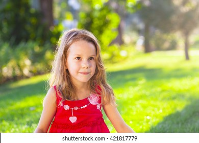 Portrait of a funny little girl in the summer park