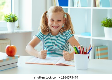 Portrait of funny little school girl at the table with books in classroom
