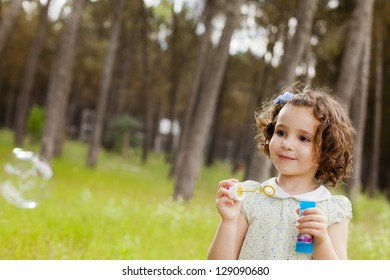 Portrait of funny lovely little girl making soap bubbles. Free space for your own bubbles.