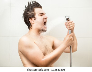 Portrait of funny man singing at shower