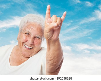 portrait of funny old woman doing a rock and roll symbol