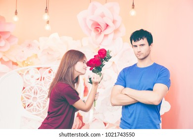 Portrait of funny photo of unhappy and annoyed young man after quarreling . relationship and marriage problems.A girl try to reconcile a man. Valentine's day concept.