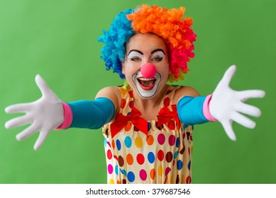 Portrait of a funny playful female clown in colorful wig stretching her hands like ready to hug and smiling, standing on a green background