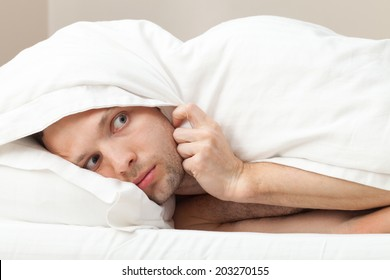 Portrait of funny scared Young Caucasian man in bed