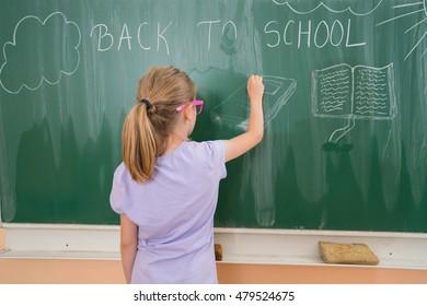 Portrait of a funny schoolgirl on blackboard background. School and education. concept idea