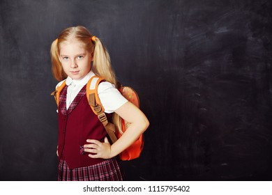 Portrait of a funny schoolgirl with schoolbag on blackboard background. School and education