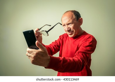 portrait of the funny senior man looking on phone