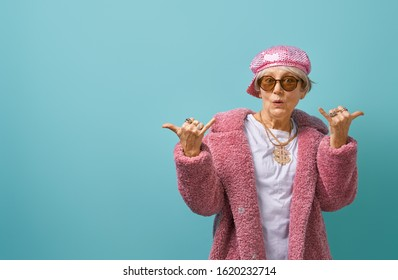 Portrait of funny senior woman on color background. Empty space for text.