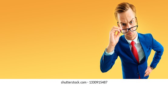 Portrait of funny skeptic businessman in blue confident suit and red tie, looking through glasses, with copy space area for some text, advertising or slogan, over yellow-orange.