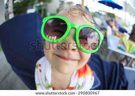 6e965784a205 Portrait of a funny smiling baby with glasses. Fish-eye lens. Focus on