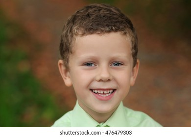 Portrait of funny smiling kid with deep grey eyes