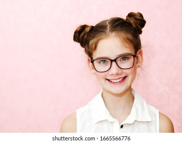 Portrait of funny smiling little girl child wearing glasses isolated on a pink background