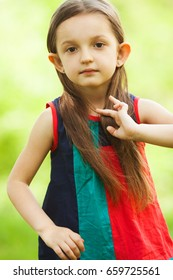 Portrait of funny, sweet, little, charismatic girl touching her long hair. Close up. Copy-space. Outdoor shot