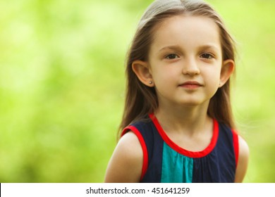 Portrait of funny and sweet little girl outdoors with curly hair in the wind. Close up. Copy-space
