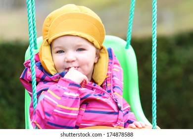 Portrait of funny toddler girl in multicolor jacket and orange hat rocking outdoors on the swing