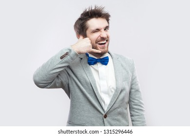 1a735c083f32 Portrait of funny winking happy handsome bearded man in casual grey suit  and blue bow tie
