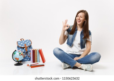 Portrait of funny woman student in denim clothes showing OK sign, blinking sitting near globe, backpack, school books isolated on white background. Education in high school university college concept