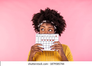 Portrait of a funny young African American girl in hiding behind a menstrual periods calendar and looking away at copy space isolated over pink background. Female Period calendar