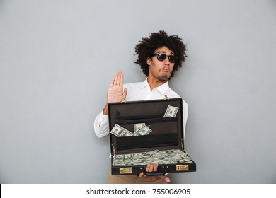 Portrait of a funny young afro american man in sunglasses holding briefcase full of money banknotes isolated over gray background
