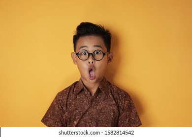 Portrait of funny young Asian boy looking at camera with open mouth and big eyes, shocked surprised expression against yellow background