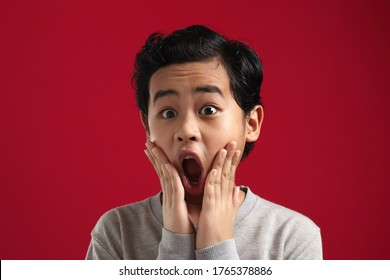 Portrait eines lustigen jungen Asiaten Jungen, der Kamera mit offenem Mund und großen Augen anschaut, schockierter, überraschter Ausdruck auf rotem Hintergrund