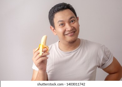 Portrait of funny young Asian man smiling while holding small banana